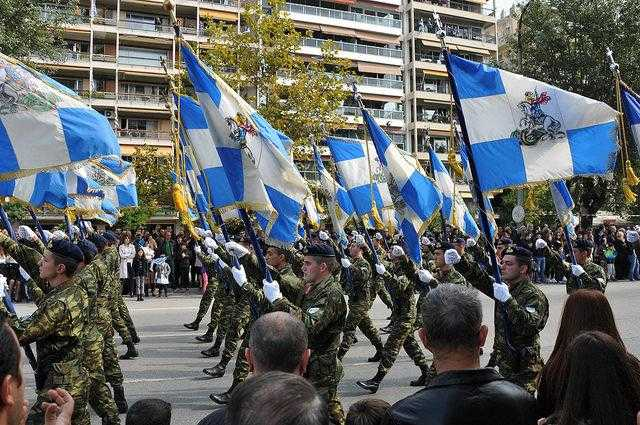 Greek soldiers marching with blue and white flags