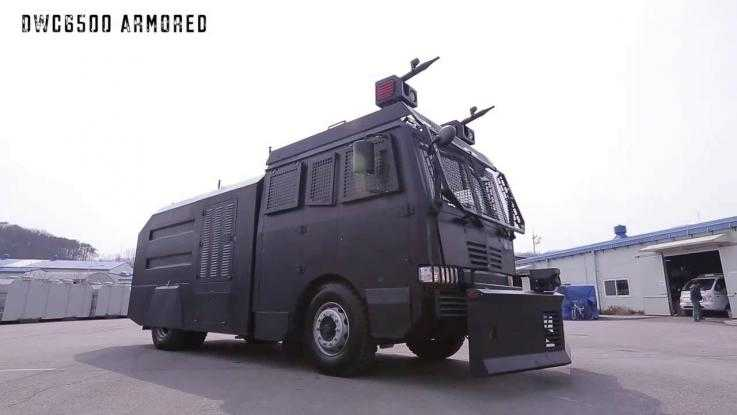A Daeji water cannon sat parked in a car park. The vehicle is black with shielded windows and two water cannons on top.