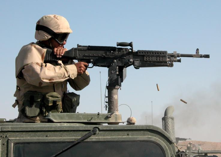 A soldier fires a vehicle mounted machine gun