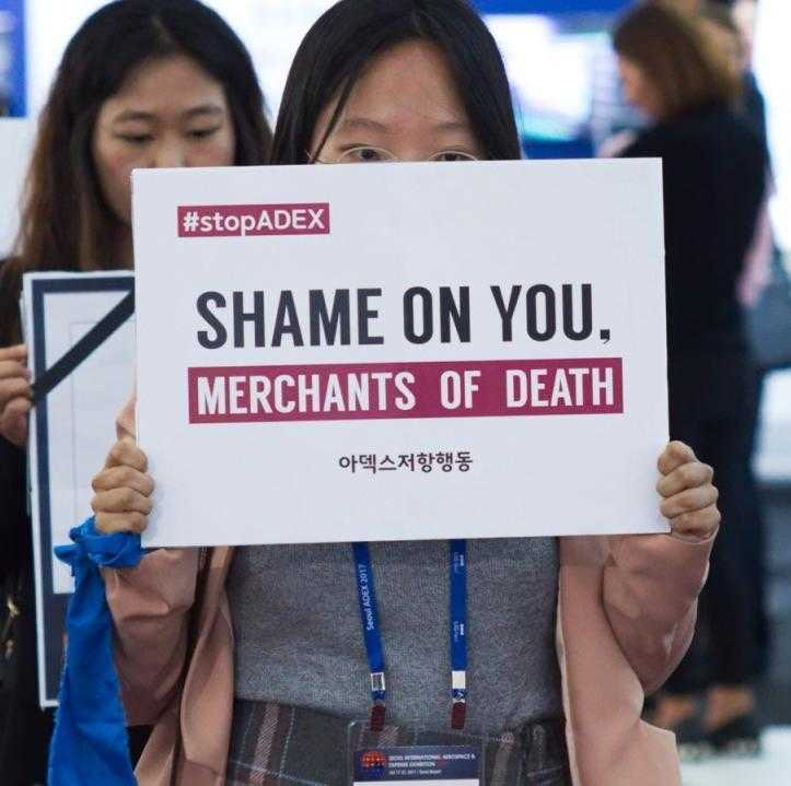 "An activist in Seoul holds a ""shame on you"" banner during the ADEX arms fair"