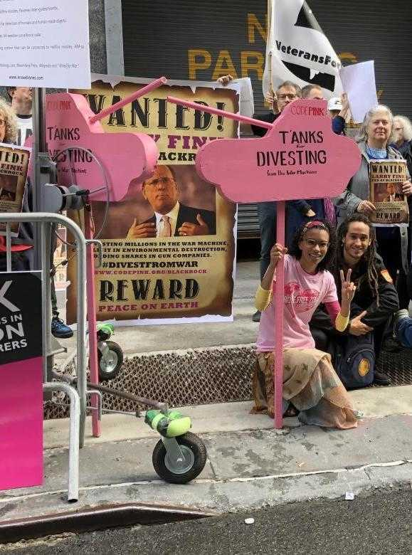 Protesters hold pink tank-shaped banners outside the Blackrock meeting