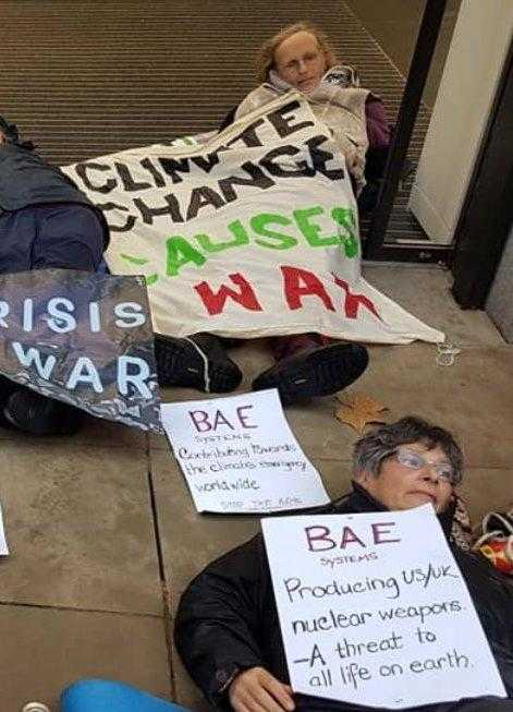 Activists lie on the floor holding banners about climate change and militarism