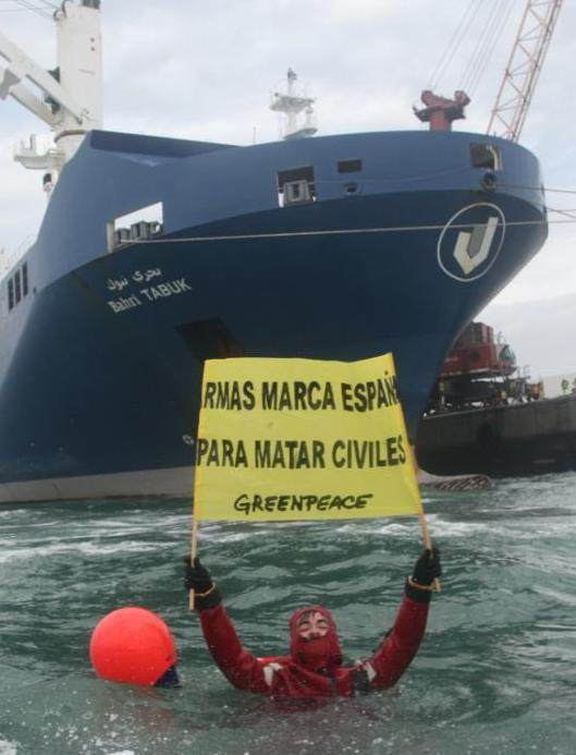 A greenpeace activist in the water in front of a boat, loaded with weapons destined for Saudi Arabia