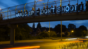 "Protesters hold banners with small lights reading ""Hands up don't shoot"" over a road"