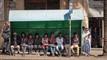 People sitting waiting at a bus stop