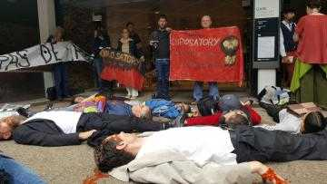 A large group of people lie on the floor in front of banners outside the Eurosatory arms fair