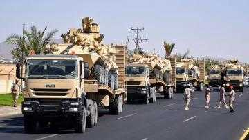 The image shows a line of heavy trucks carrying armoured vehicles.