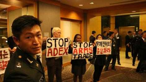 International activists inside the arms dealers welcome dinner at ADEX 2015 in Seoul