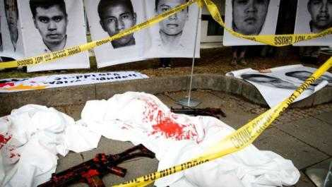 "Images from those killed or dissappeared in Mexico. A toy gun covered in blood is in the foreground, and ""crime scene"" tape is draped across."