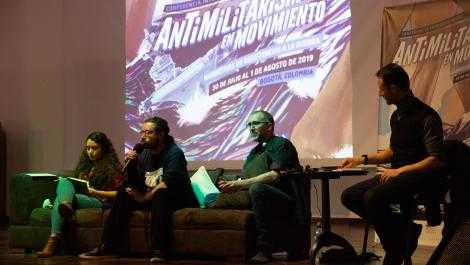 "Four people sit in front of a screen with the words ""Antimilitarism in Movement"""