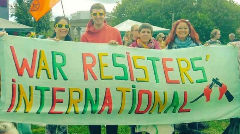 WRI members behind our banner at the festival of resistance against DSEI!