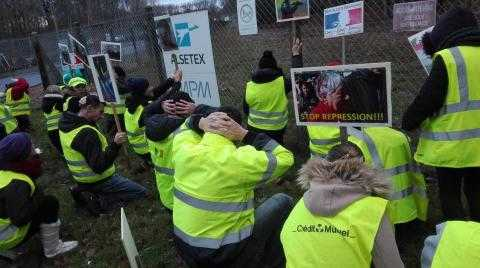 Several dozen protesters wearing yellow vests kneel on the grass outside a fence. On the fence is the sign of the company, Alsetex.  Several protesters are holding signs depicting injuries caused by the companies products