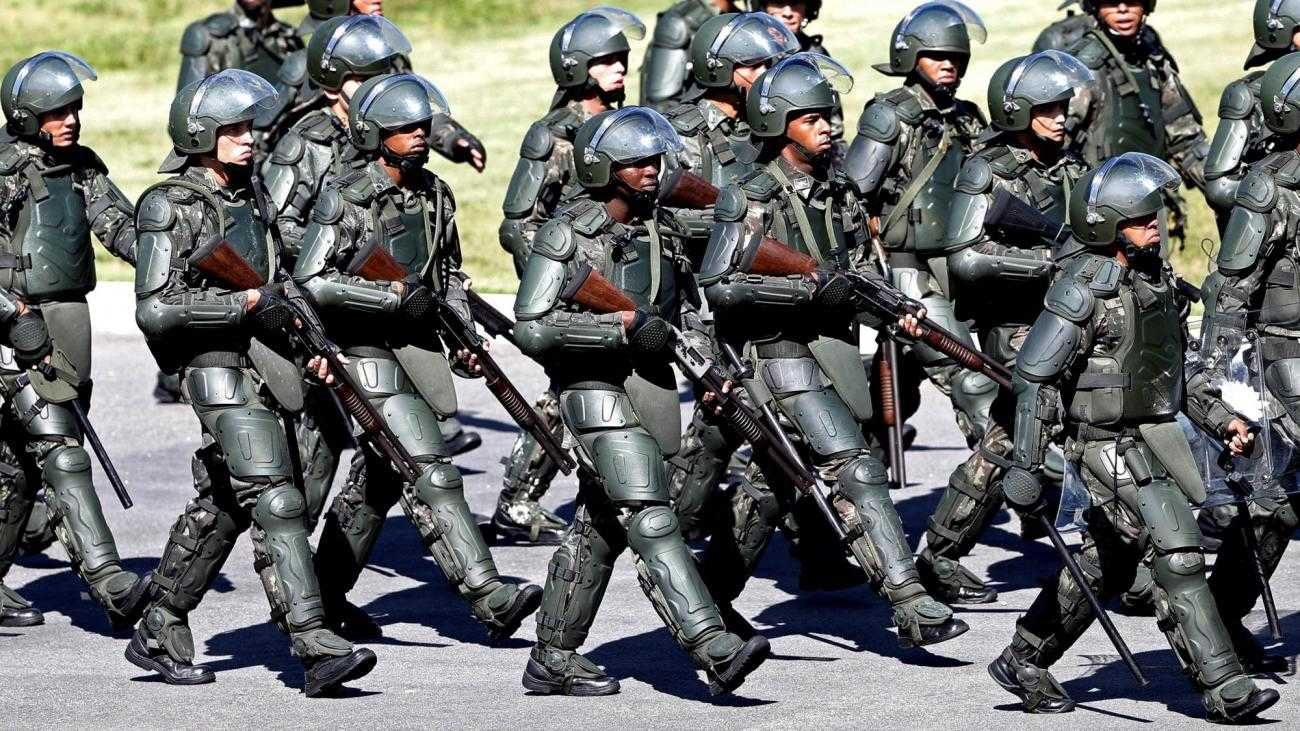 A large group of heavily armed and armoured police in Brazil during the world cup, march in formation.