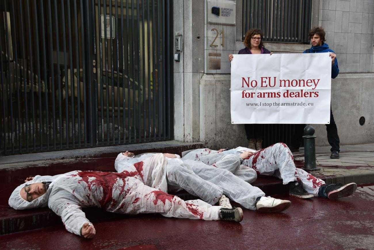 Activists in Belgium protest against the arms industries access to the EU, pouring blood on the street.