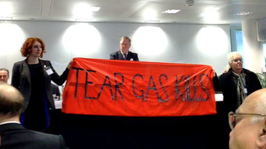 "Activists interrupt a shareholder meeting with a banner that reads ""Tear Gas Kills"""