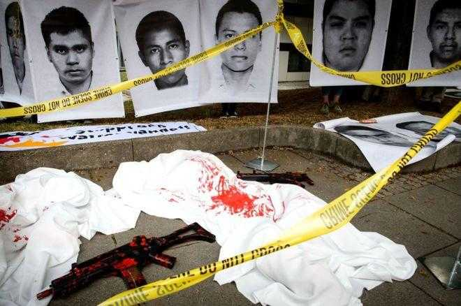 "Images of the missing or murdered Mexican teachers in front of a ""crime scene"" with pretend guns covered in blood, surrounded by yellow crime scene tape."