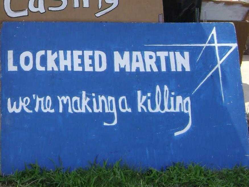 "A protest banner mimic the Lockheed Martin logo. The sign reads ""Lockheed Martin: we're making a killing"""