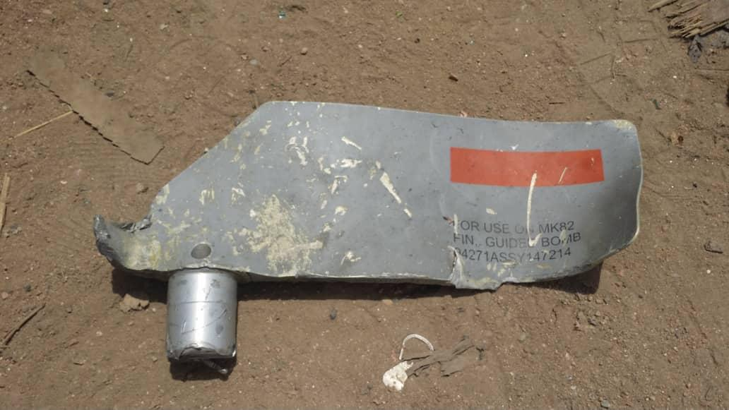 A piece of metal marked with identification numbers lies on sandy ground