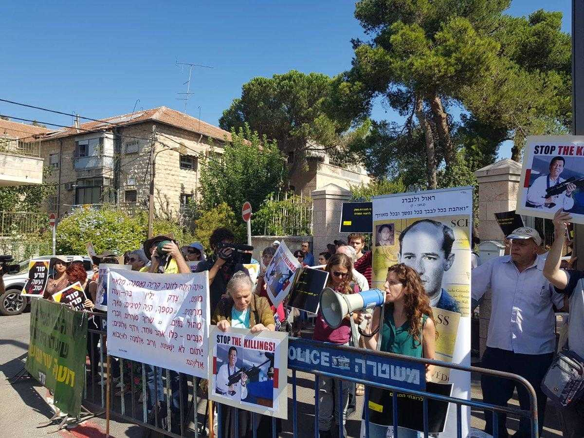 "A large group of people gather on a street behind a security cordon. There are trees in the background. The people are holding banners and signs which read ""stop the killing"""