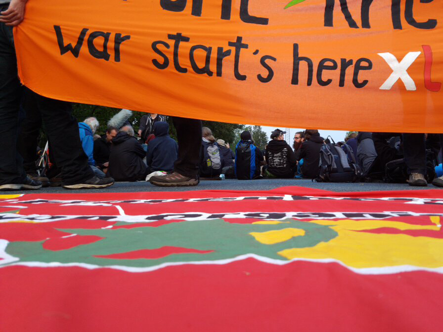 "An orange banner at the top reads ""War Starts Here"". Another banner lies on the floor. Between them is a line of people sat with their backs to the camera, blocking a road."