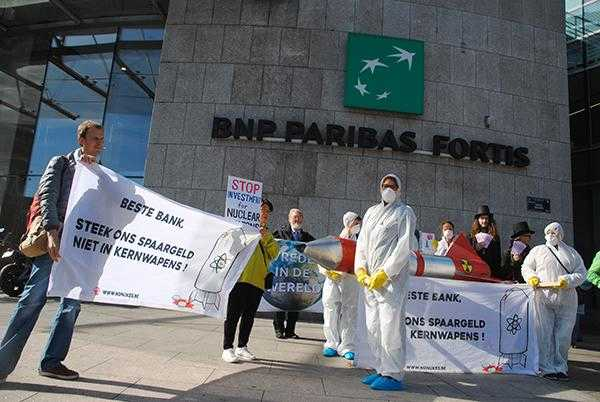 "Activists dressed in white ""bio hazard suits"" and wearing gas masks hold banners reading ""don't invest in nuclear weapons"" outside a building with the BNP Paribas logo"