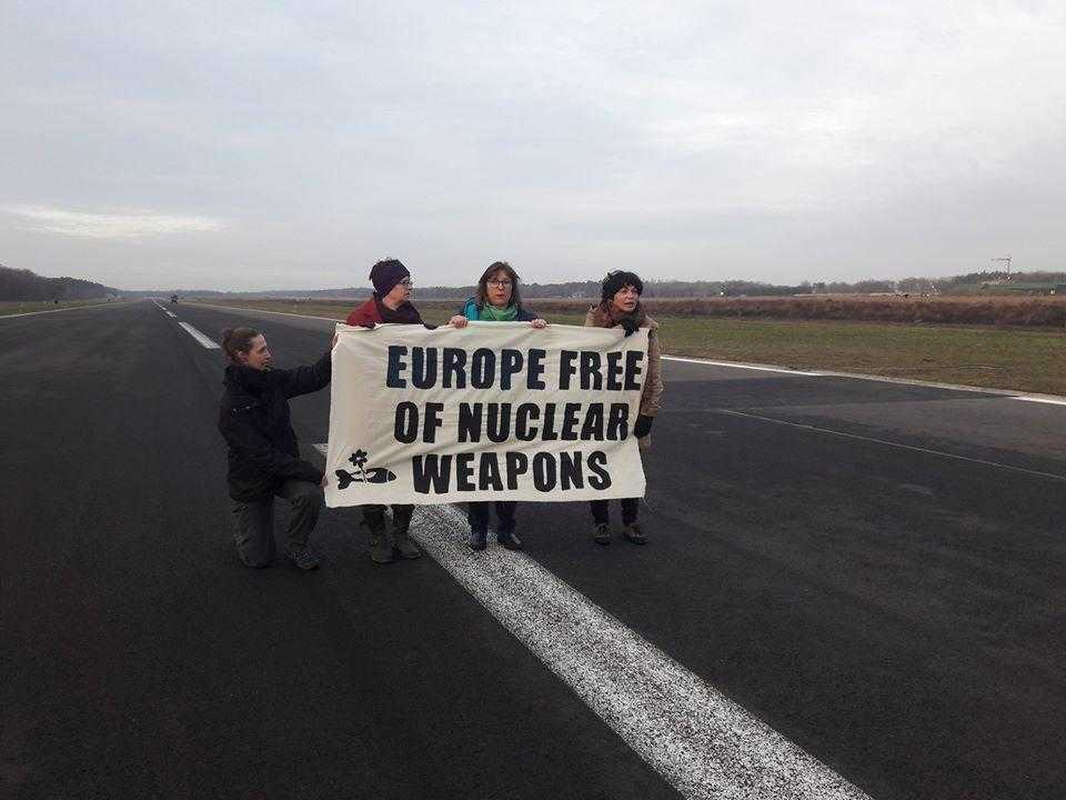 "Four activists stand in a runway with a banner reading ""Europe free of Nuclear Weapons"""