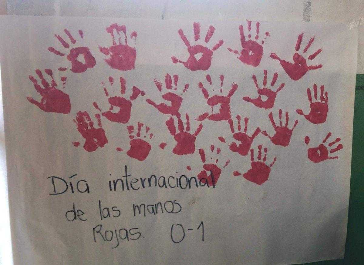 "A sign covered in red hands reads ""International red hand day"" in Spanish"