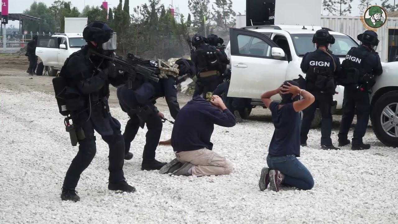 French police take part in a live demonstration at Eurosatory. Heavily armed police officers stand around two men knelt on the floor with their hands on their heads.