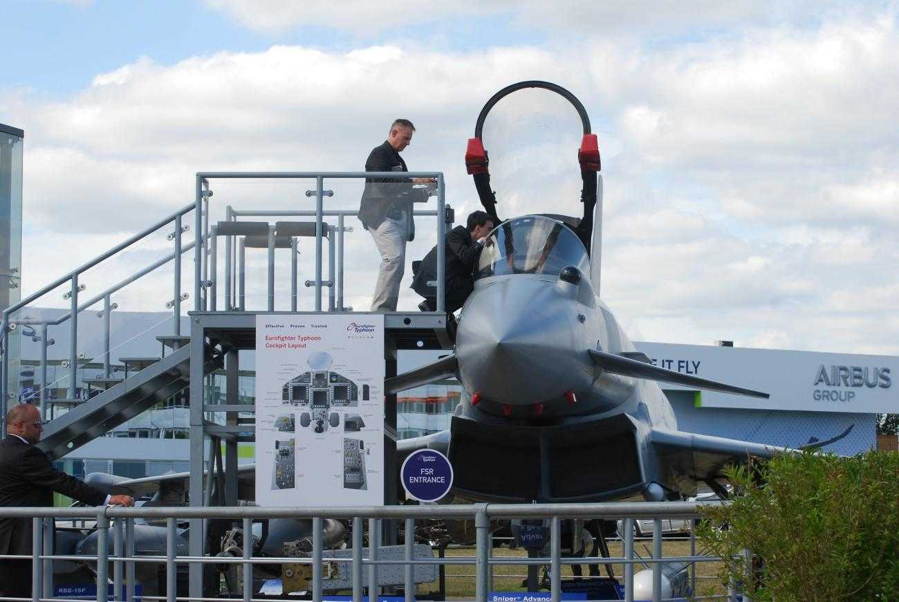 Two men inspect a plane at Farnborough International