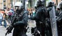 Heavily armed police officers in the UK face protesters. One is carrying a large weapon, another a shield.