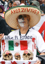A woman in Mexico protests on the anniversary of the disappearance of 43 students in Mexico