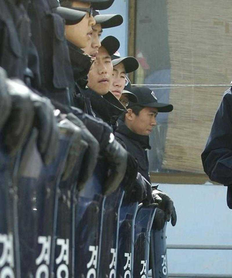 An officer with a walkie-talkie inspects a line of police conscripts wearing blue uniforms and baseball caps and resting their leather-gloved hands on transparent riot shields emblazoned with the word 'police' in Korean script