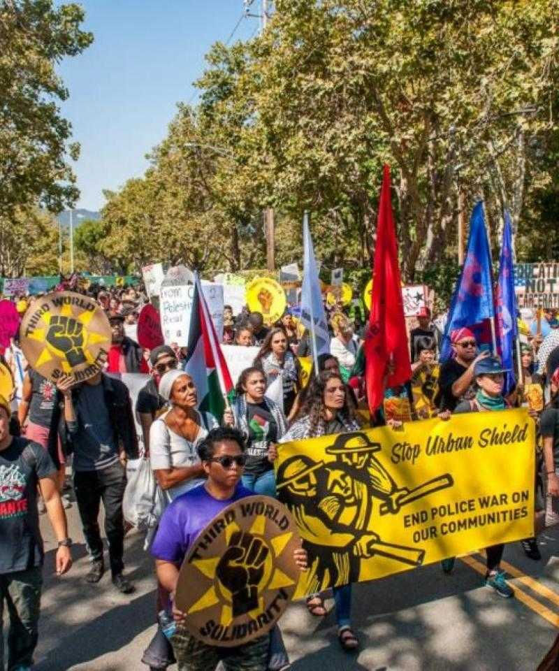 A crowd marches down a tree-lined avenue holding colourful banners and flags.  The yellow banner at the forefront of the picture reads 'Stop Urban Shield: End Police War on Our Communities'.