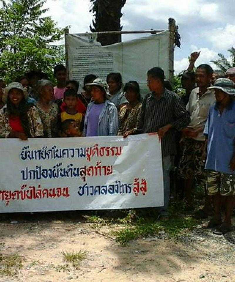 Villagers of Khlong Sai Pattana Community. The banner reads: 'We will stand for justice to protect land to the end. Stop evicting the poor. The Khlong Sai people will fight'.