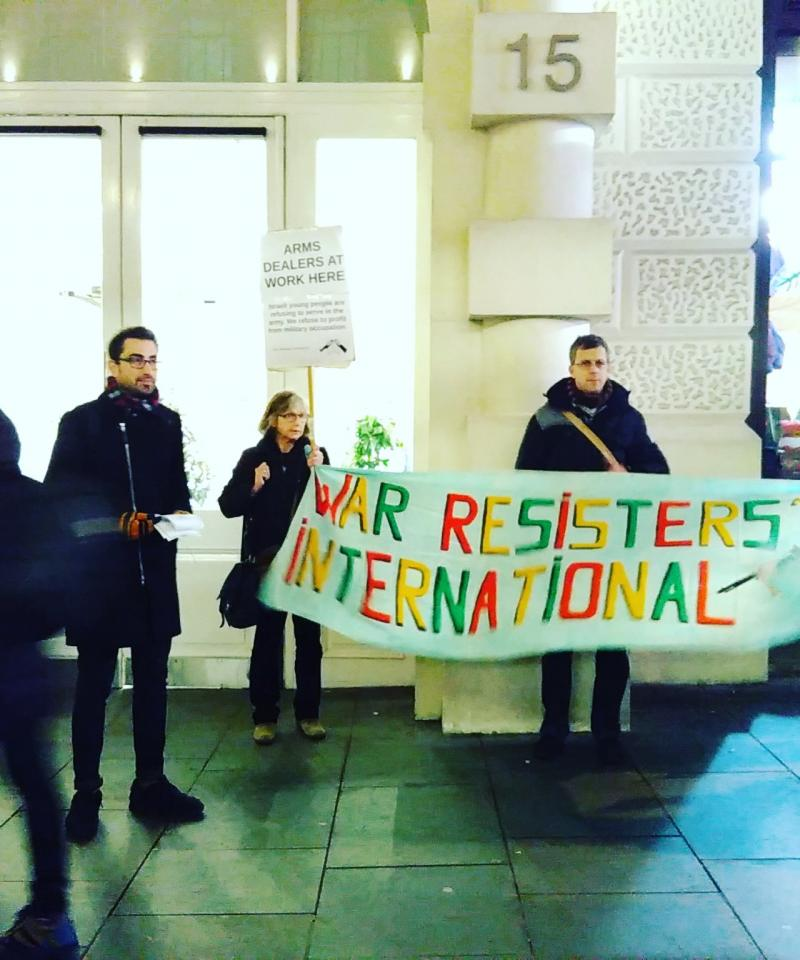 Several people holding a 'War Resisters' International' banner, and handing out leaflets, outside a building