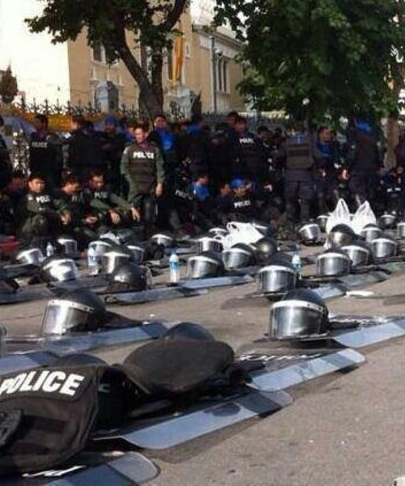 Police stand and sit by the side of the road.  Their shields and helmets are laid out in rows on the road.