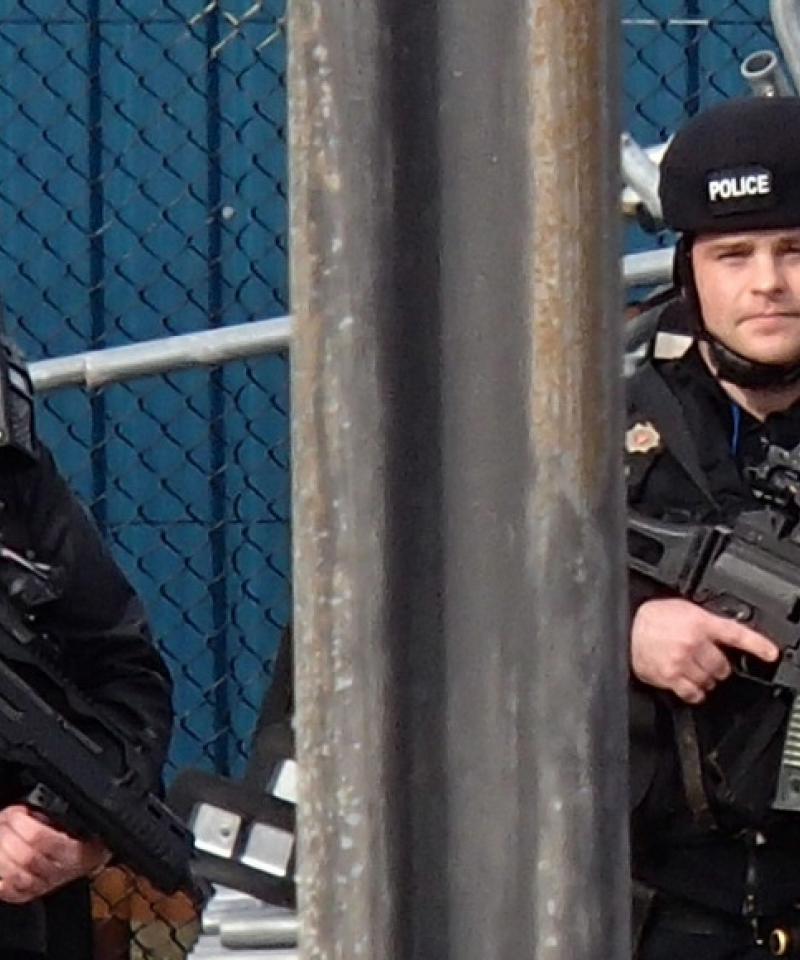 Two members of the heavily armed Civil Nuclear Constabulary stand behind a fence. They are wearing helmets, bullet proof vests, and carrying large guns.