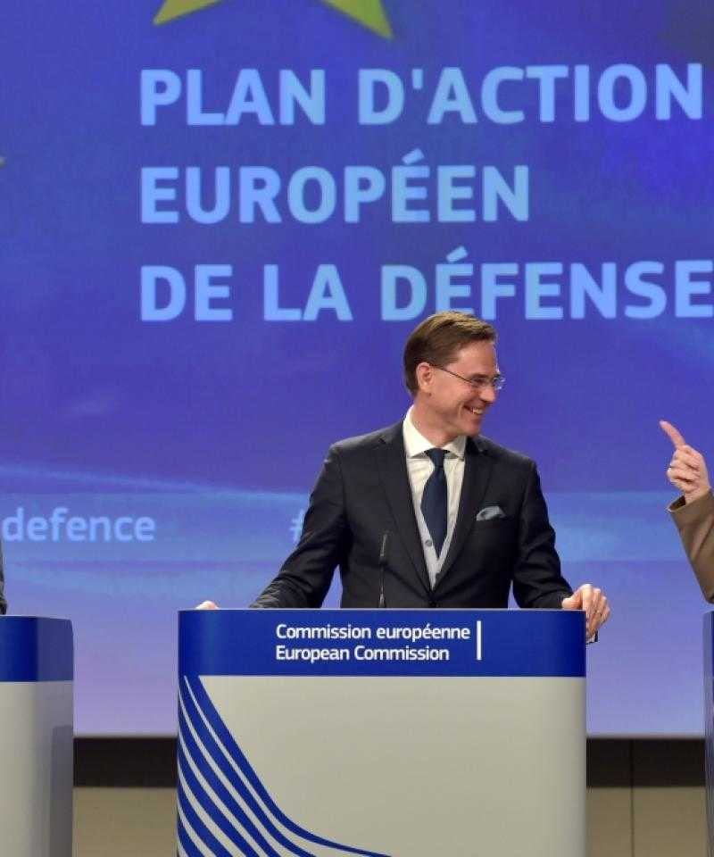 "Three politicians stand in front of a sign saying ""Plan of Action: European Defence Fund"" in French"