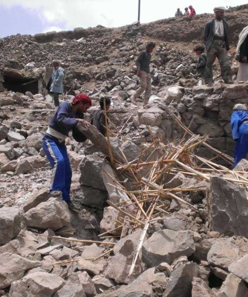 Around a dozen people climb over the rubble of demolished buildings in Yemen.