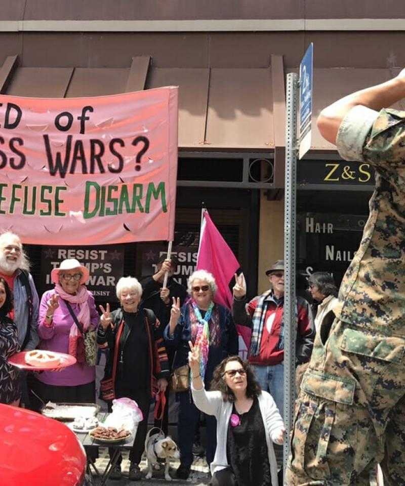 A group of people holding a pink banner saying 'Tired of Endless Wars? Resist, Refuse, Disarm' outside a recruitment centre, with a soldier taking a photo of them with a phone