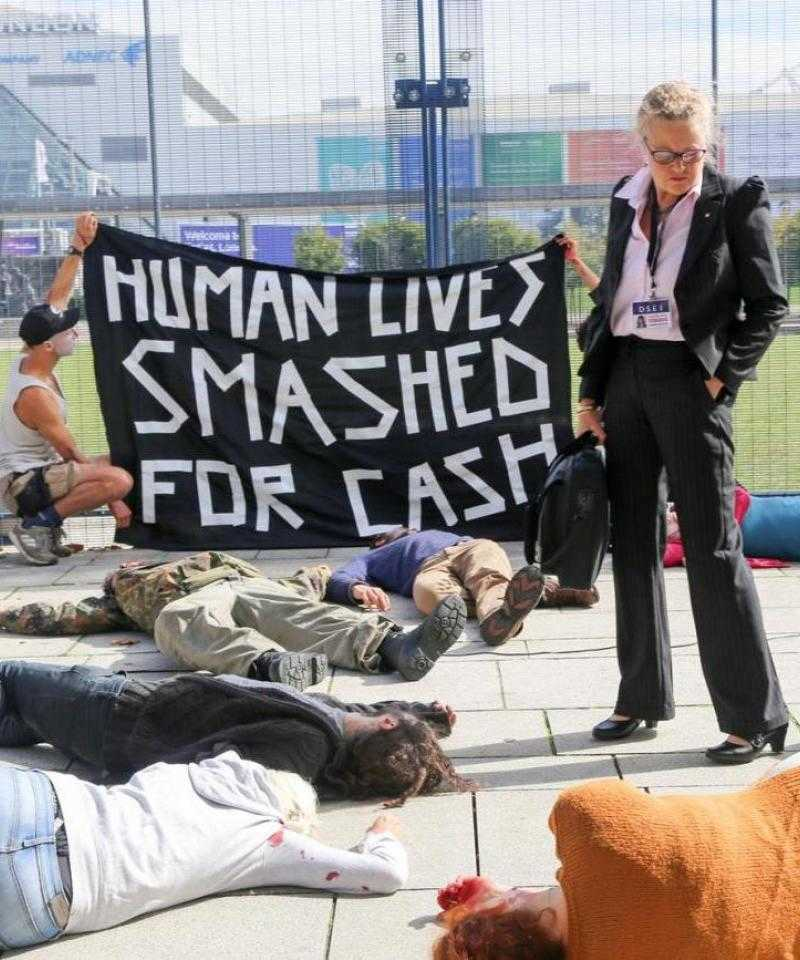 "A die-in at DSEI 2017. People lie on the floor, while a woman dressed in business clothing looks down. Behind her activists hold a sign that reads ""Human lives smashed for cash"""