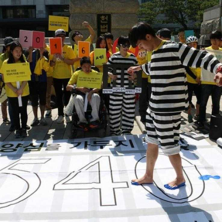 Protests in Seoul against the imprisonment of conscientious objectors; a man dressed as a prisoner walks across across a banner with 540 written on (the number of COs then in jail)