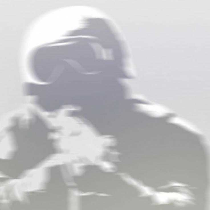 The top half of a silhouetted figure wearing a helmet and goggles points a gun towards the camera.  The image is grey and blurred.