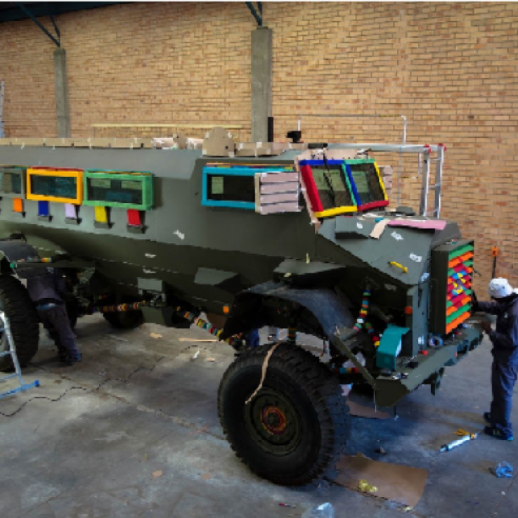 A largely undecorated Casspir stands in a warehouse with brick walls and a concrete floor.  The khaki paintwork of the Casspir is interrupted by bright, multicoloured beading on the window frames and grille.  An artist in overalls is working on the beading on the grille and near the back wheel there is a platform ladder.