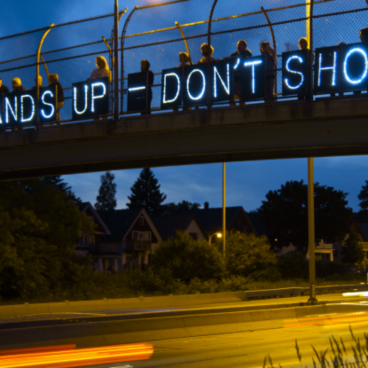 "Protesters hold banners with small lights reading ""Hands up don't shoot"" on a bridge over a road at dusk"