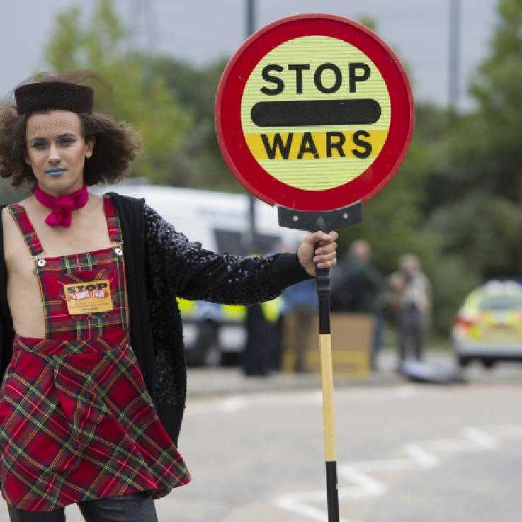 "Someone blocks a road outside the DSEI arms fair with a traffic sign reading ""stop wars"""