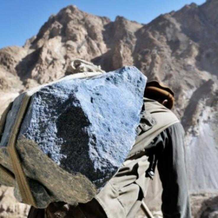 A man carries a large piece of lapis, a semi-precious stone, in Afghanistan.