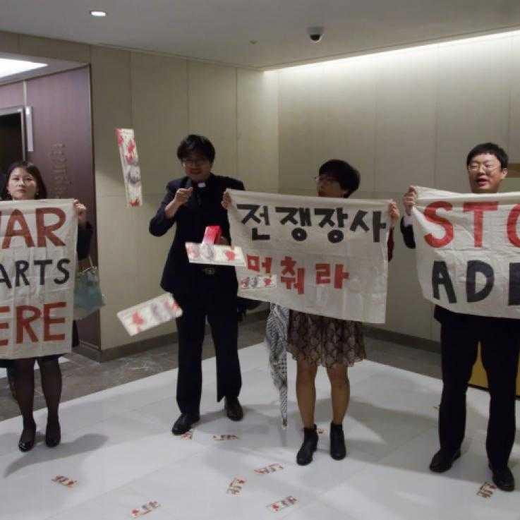 Four people holding up signs saying 'Stop ADEX' in English and Korean. One of the people is wearing a dog collar.