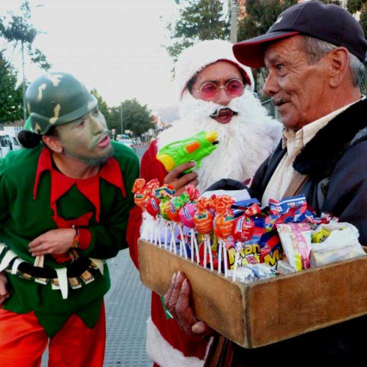 Antimilitarist activsts interview members of the public dressed as santa and christmas elves, armed with water pistols and wearing military helmets