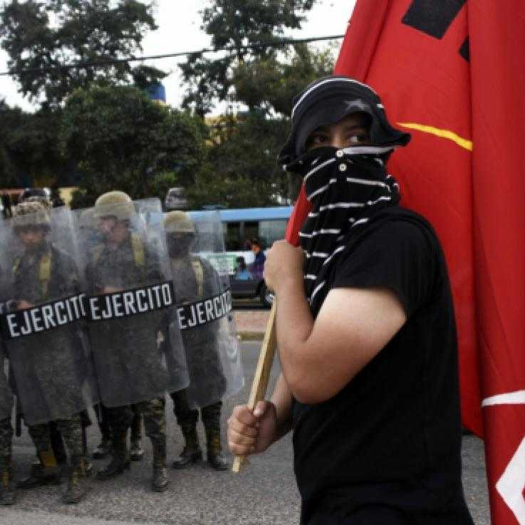 An activist with his face covered holds a red flag. He is stood in front of a line of police officers and military personnel holding shields.